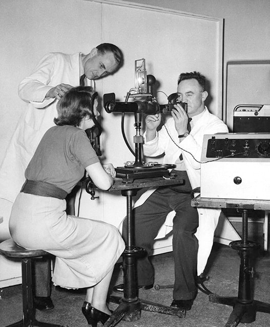 Peter Hansell (standing) with another photographer using an ophthalmic camera